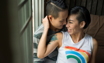 Two women in a romantic embrace. one woman is wearing a tank top with a rainbow on it.